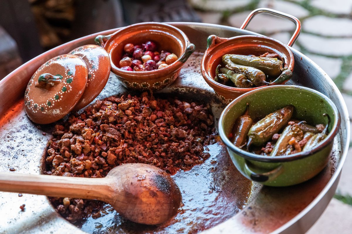 A discada for tacos, surrounded by various grilled dishes and a wooden spoon.