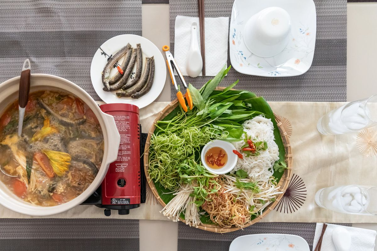 Layout of Vietnamese fish stew with a basket of noodles and vegetables.